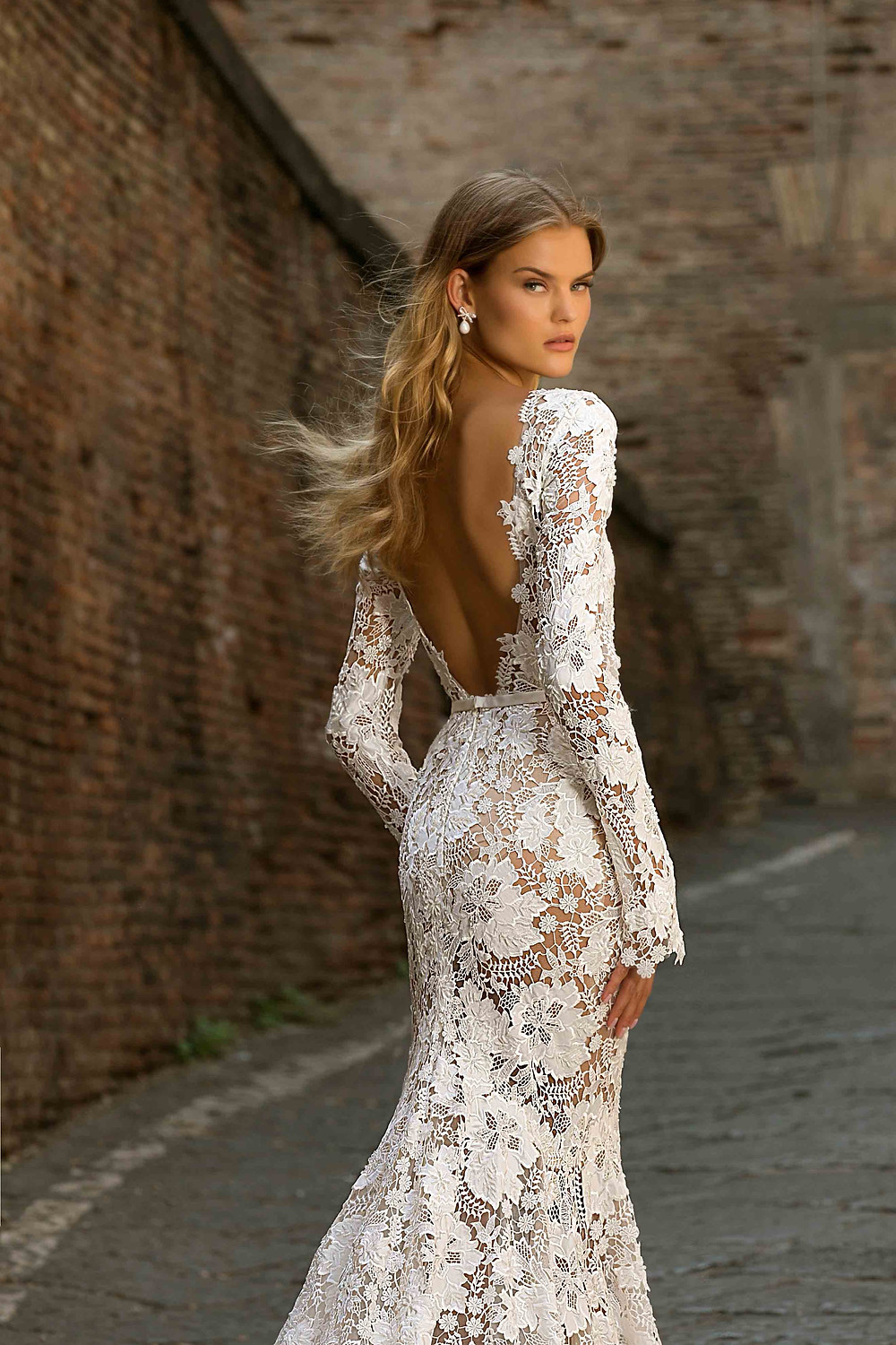 A lace mermaid wedding dress with long sleeves and a low back