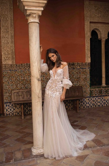 An off the shoulder, champagne, tulle A-line wedding dress with long sleeves
