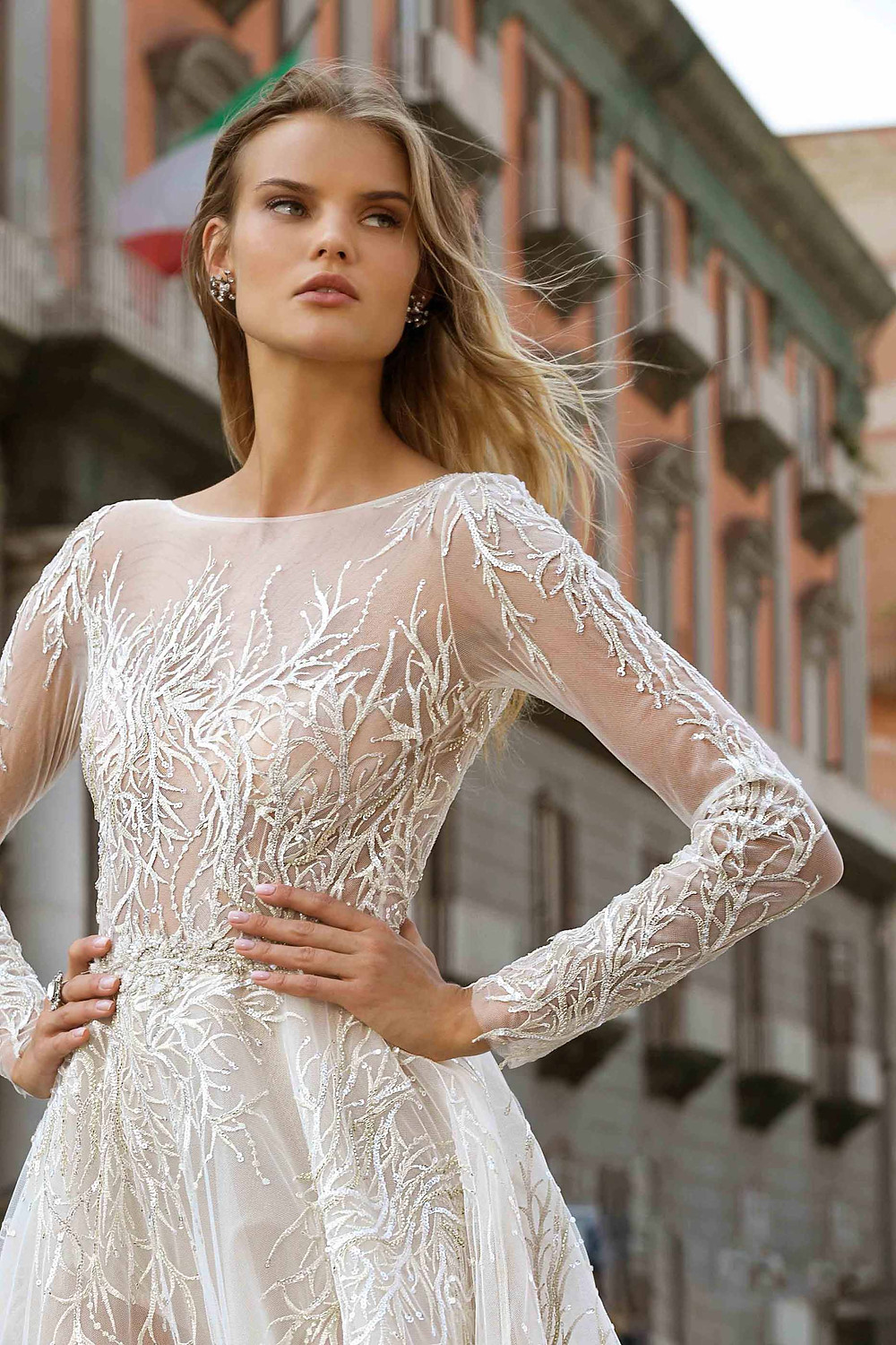 A tulle A-line wedding dress, with long sleeves, illusion neckline and crystals