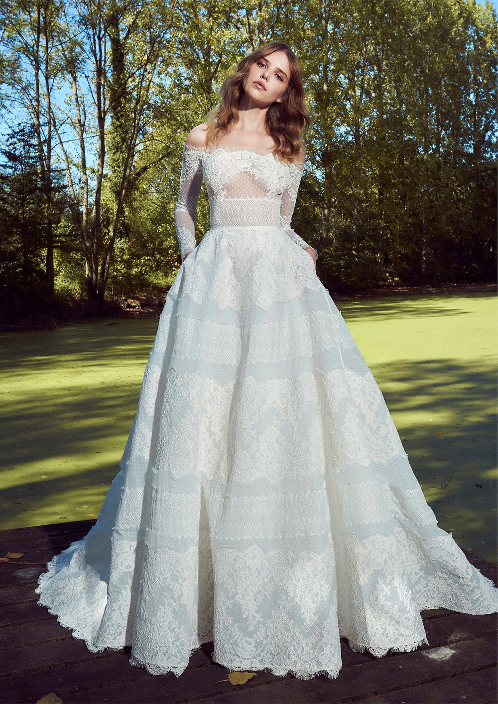 A Zuhair Murad off the shoulder boho lace ball gown wedding dress with pockets and long sleeves