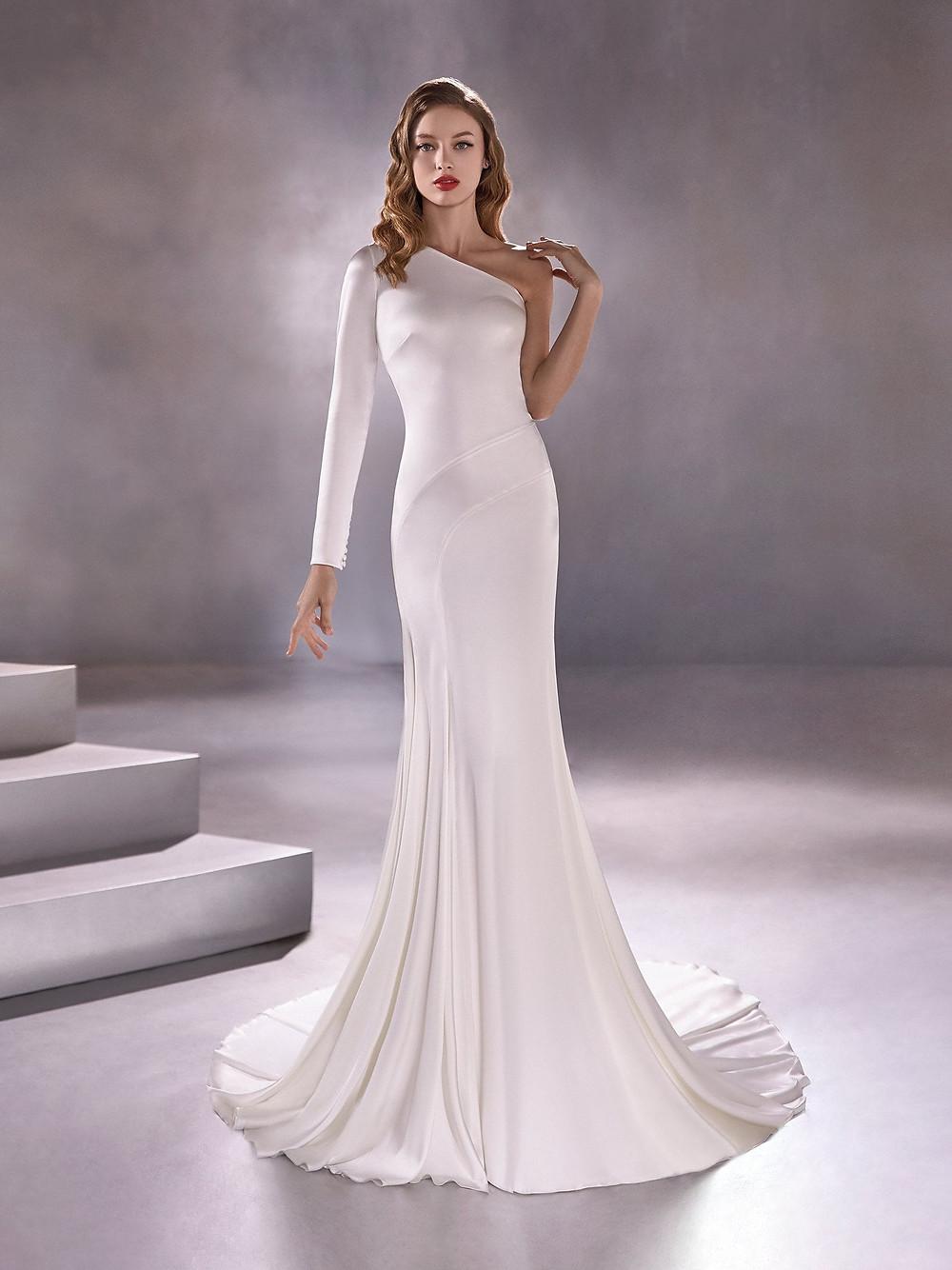 A Pronovias clean long sleeve, one shoulder sheath wedding dress