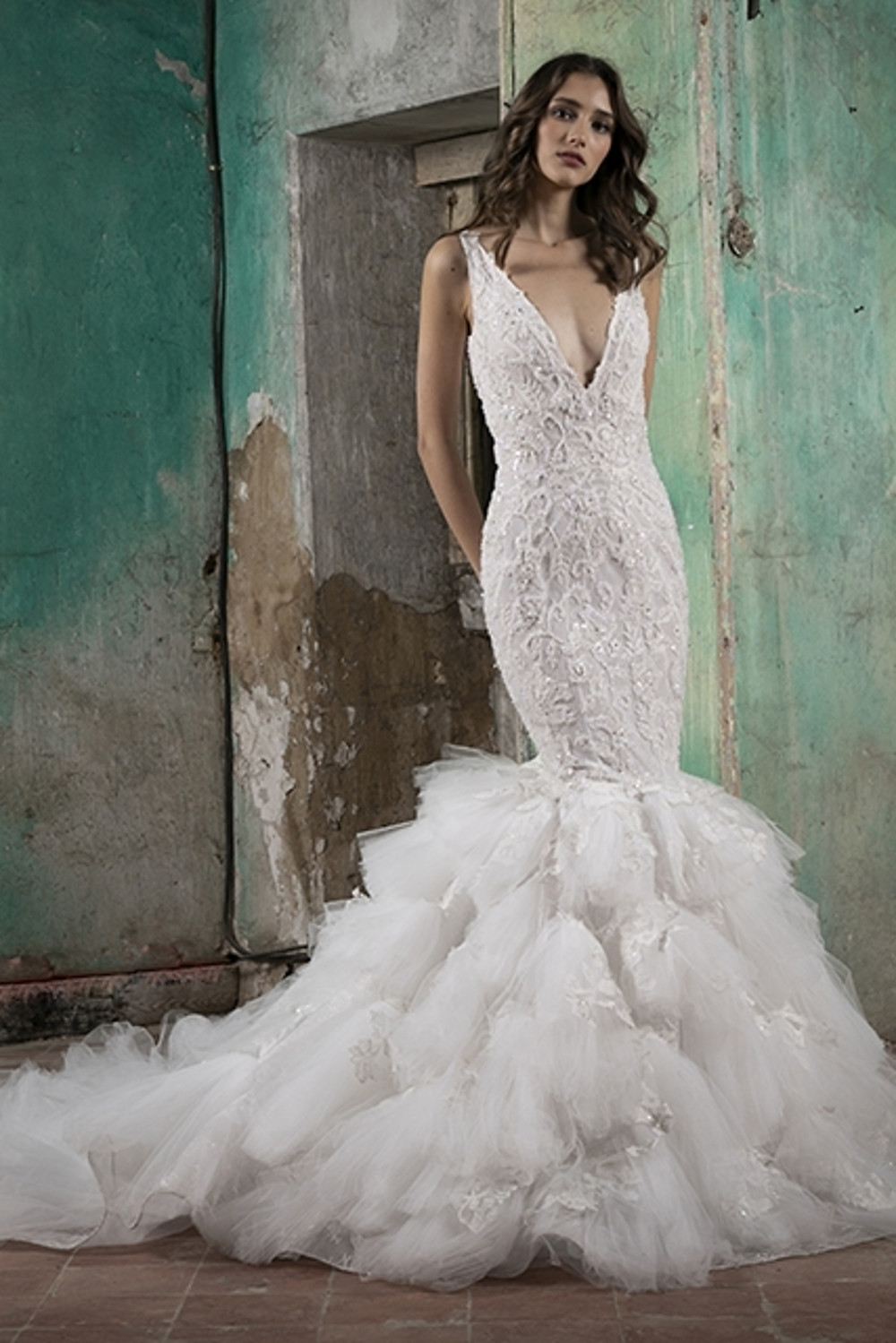 A fitted mermaid wedding gown enriched with beaded embroidery accentuated with tulle detailing around the hem