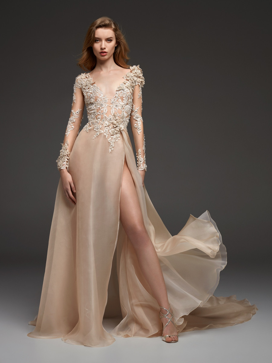 A Pronovias champagne A-line wedding dress, with high slit, long illusion sleeves and lace