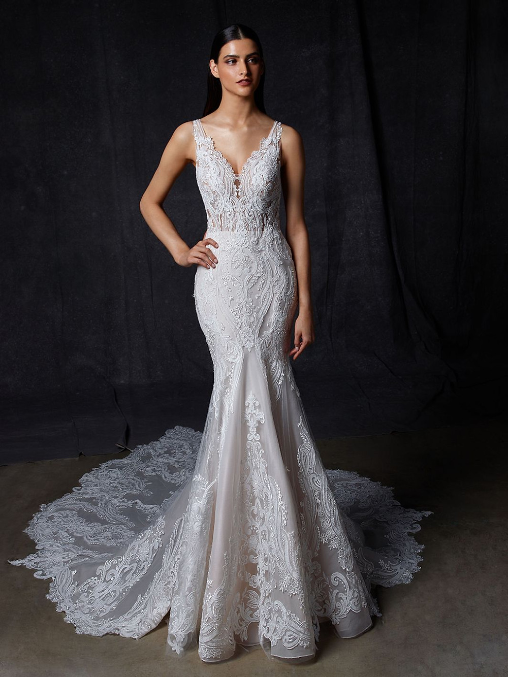 An Enzoani lace, v neck mermaid wedding dress with straps and a long train