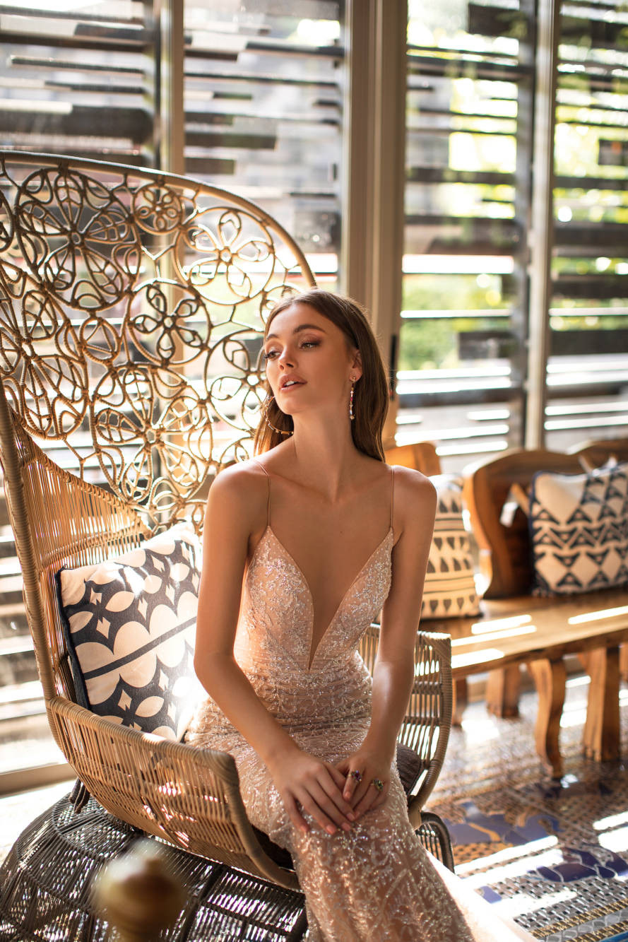 A peach mermaid wedding dress, with crystals, low v neckline and thin straps