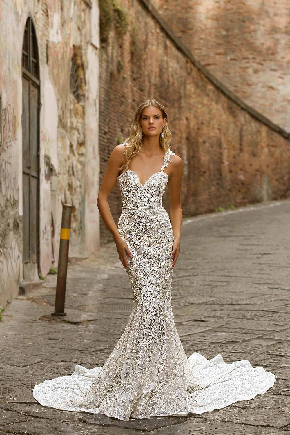 A lace mermaid wedding dress, with straps, a sweetheart neckline and and flowers