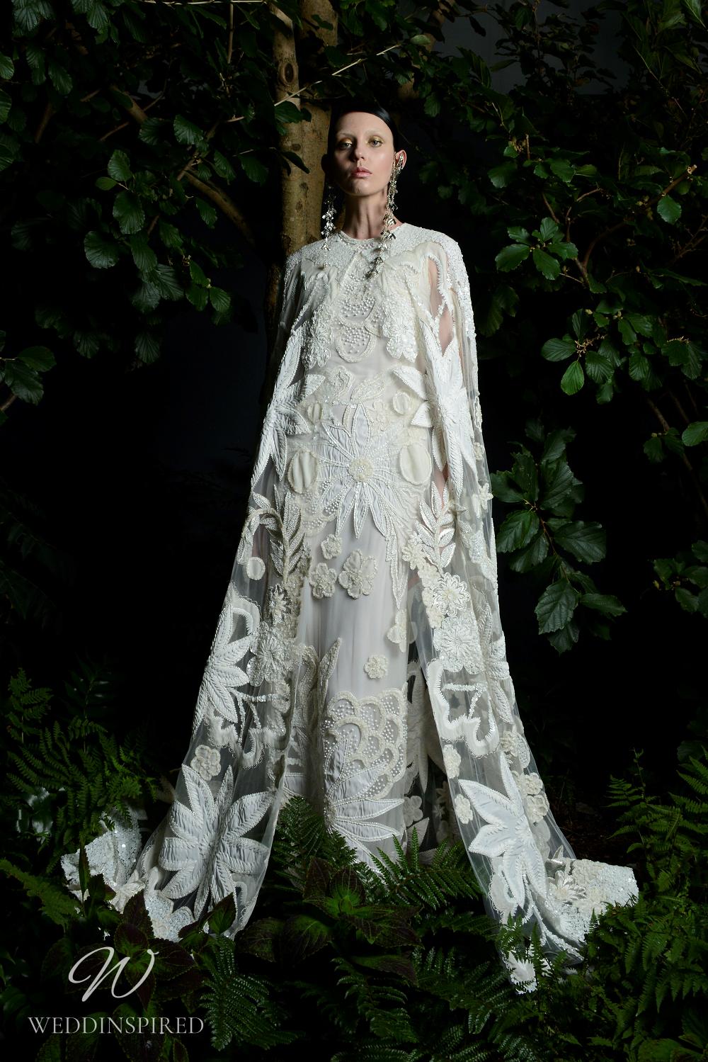 A Naeem Khan Fall 2021 sheath wedding dress with bold floral print and a cape