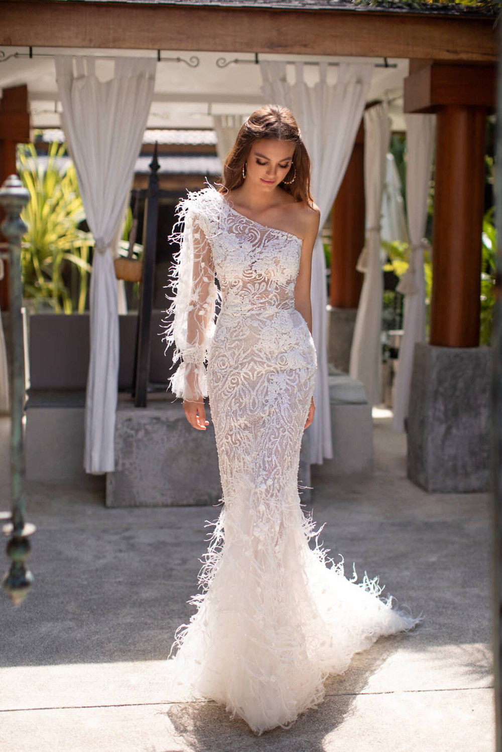 A one shoulder mermaid wedding dress with feathers and a floral print