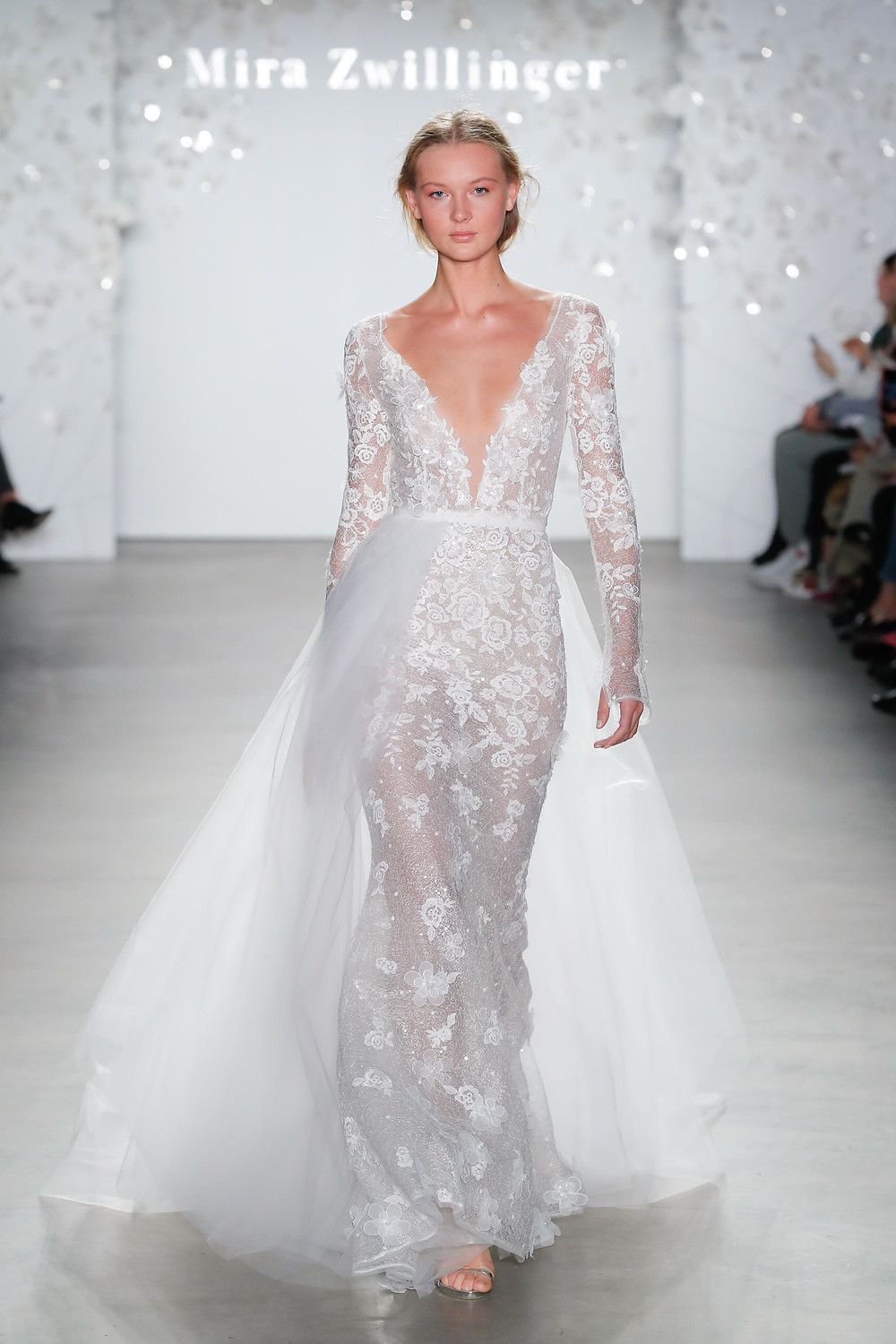 A Mira Zwillinger lace and mesh mermaid fit and flare wedding dress with long sleeves and a low v neckline