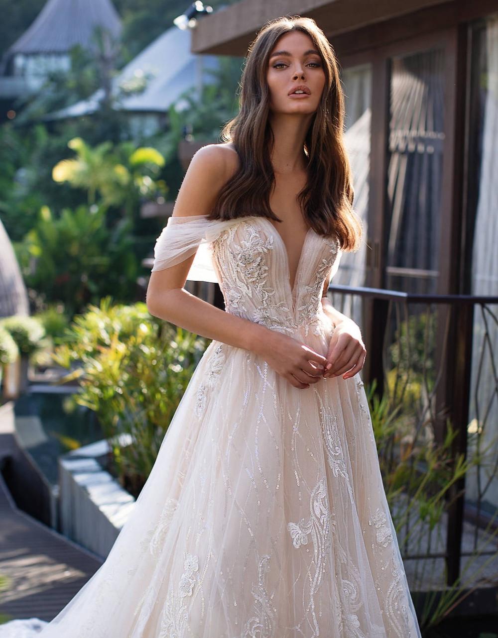 A Milla Nova off the shoulder blush pink princess ball gown wedding dress