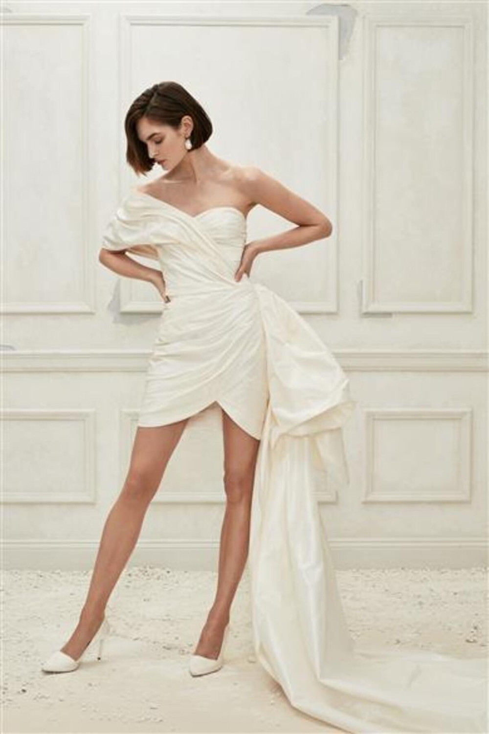 A short one shoulder wedding dress, with a large bow