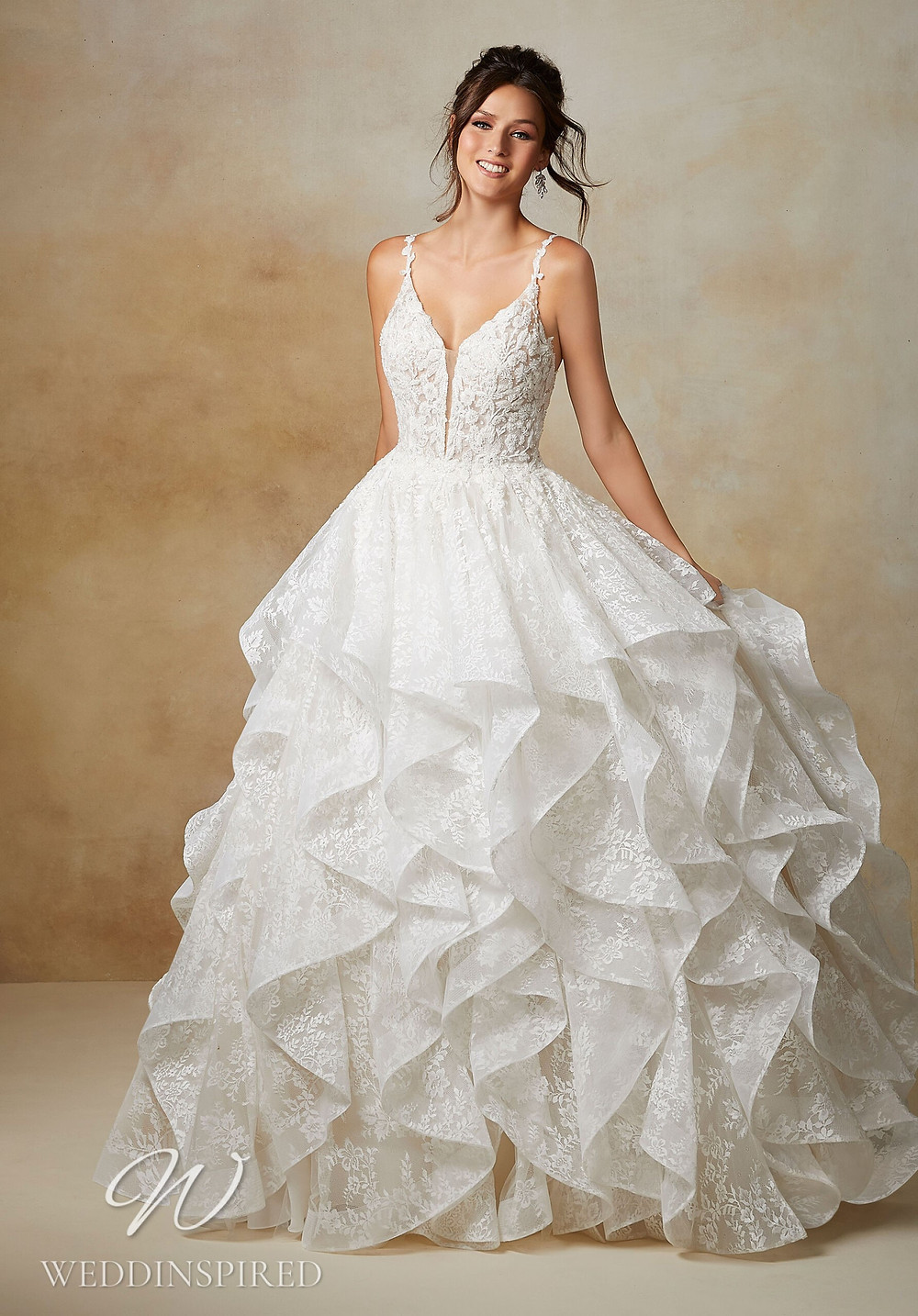 A Madeline Gardner lace princess ball gown wedding dress with a ruffle skirt and straps