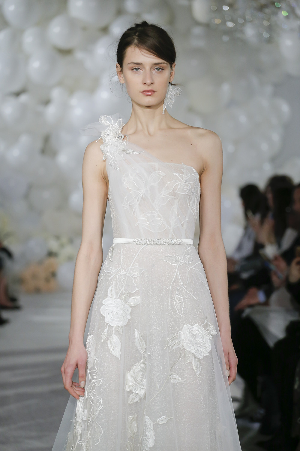 A soft, gauzy one shoulder wedding dress, with a tulle A-line skirt and floral embellishments