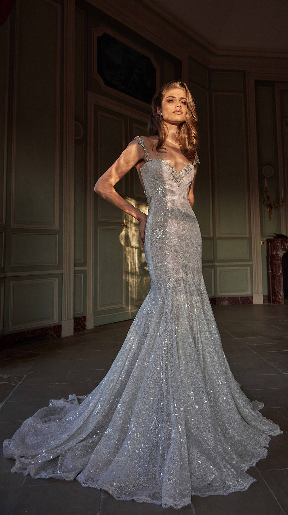 A soft mermaid silhouette and shimmery layers of sparkle tulle that reflect the light like glass, give this wedding gown a glamorous edge and a sheer low back made of delicate French lace atop a silver netting with hand-embroidered bow motifs make it ultra elegant