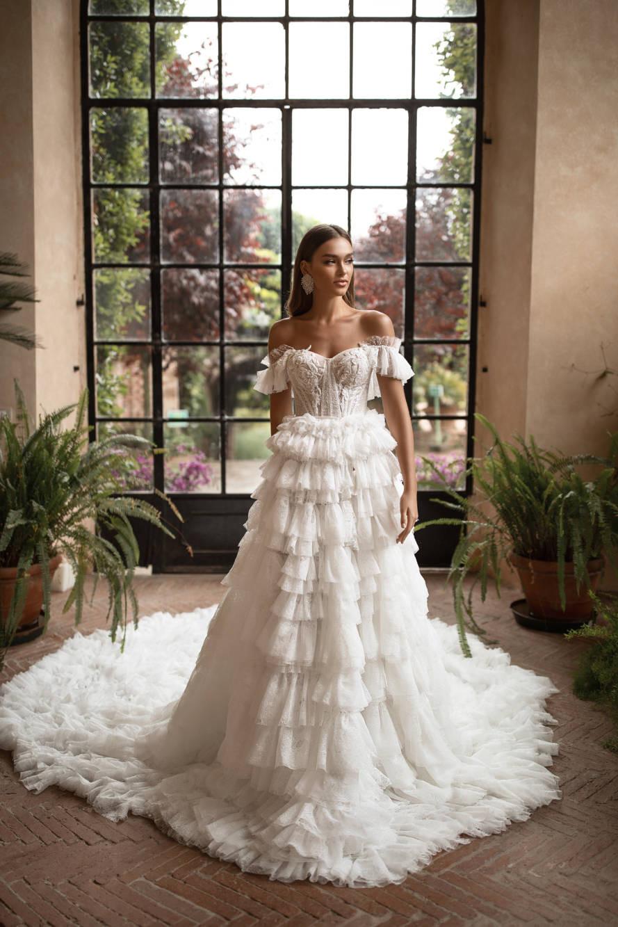 A Milla Nova off the shoulder ball gown wedding dress with a layered ruffle skirt