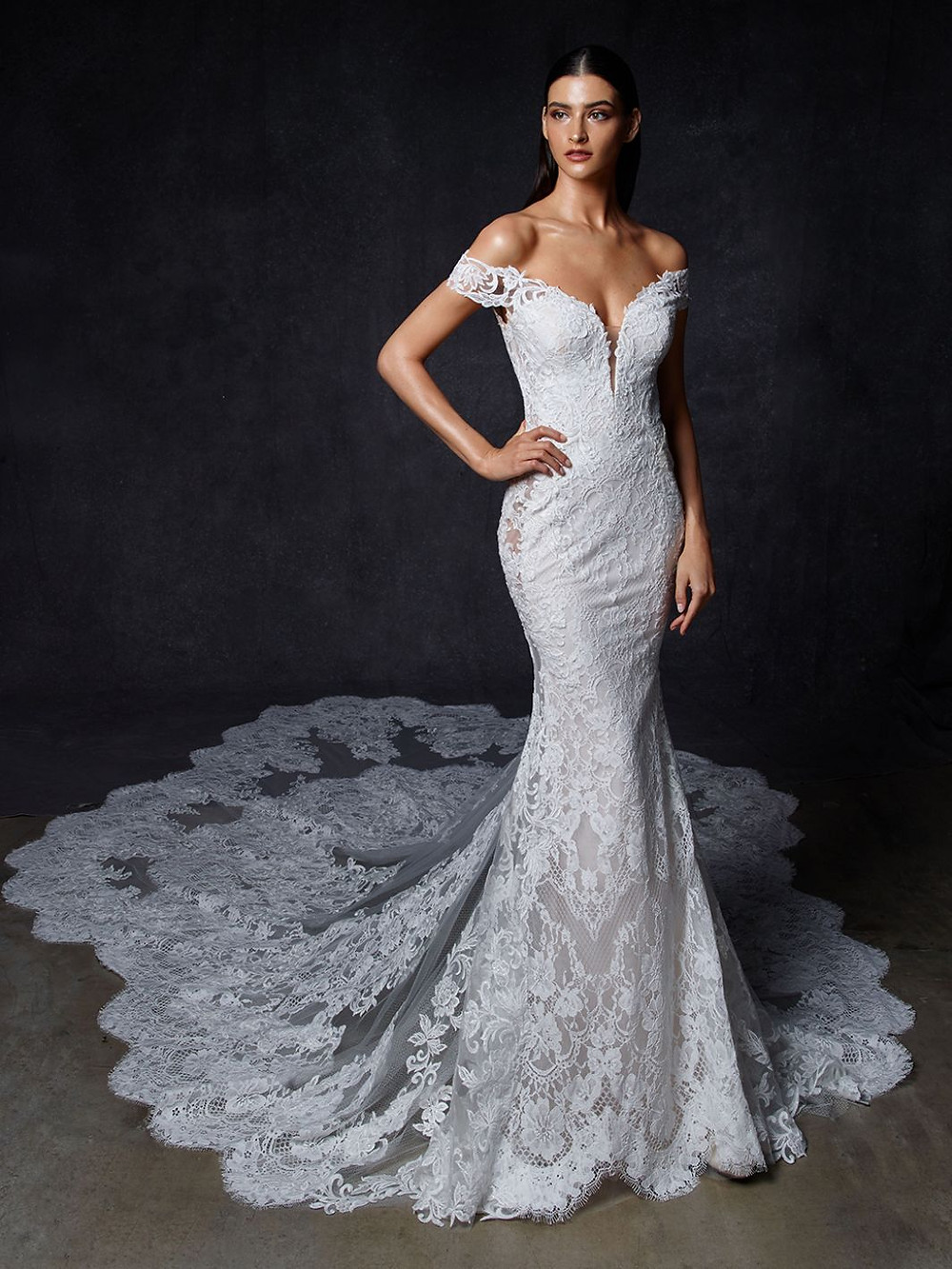 An Enzoani off the shoulder, lace mermaid wedding dress with a long train