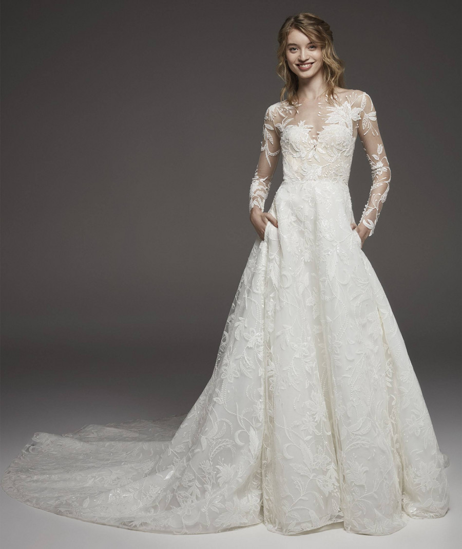 A Pronovias lace ball gown wedding dress with pockets and long illusion sleeves