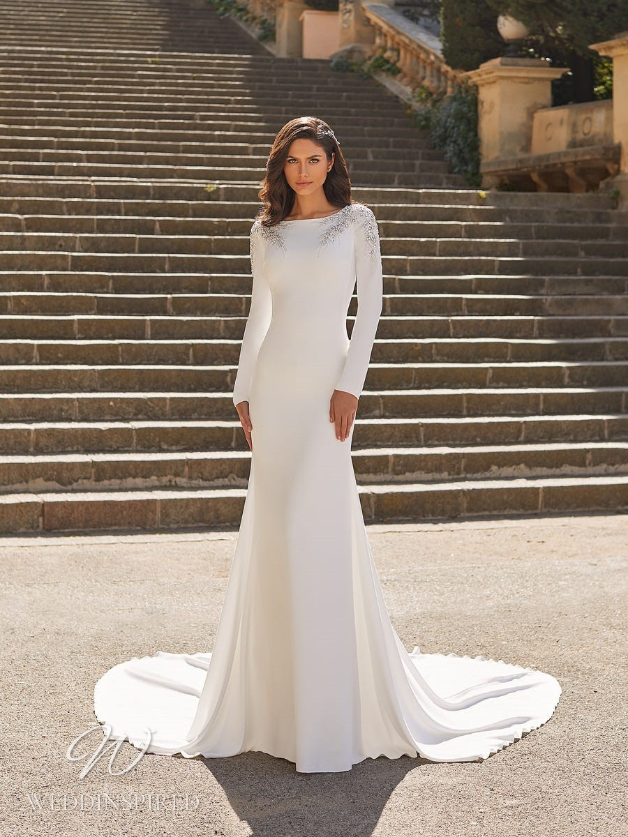A Pronovias Privée 2021 modest crepe sheath wedding dress with long sleeves, a high neck and a train