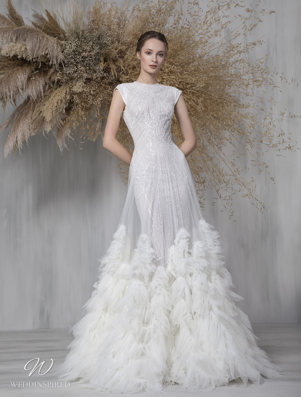 A Tony Ward 2021 mesh and tulle mermaid wedding dress with a high neck, cap sleeves and a feather look skirt