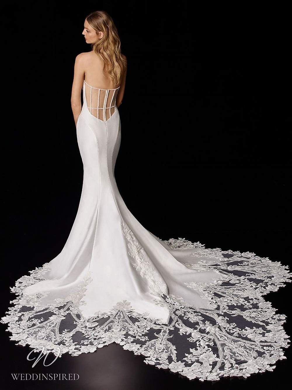 An Enzoani silk and lace mermaid wedding dress with a low back and a long lace illusion train
