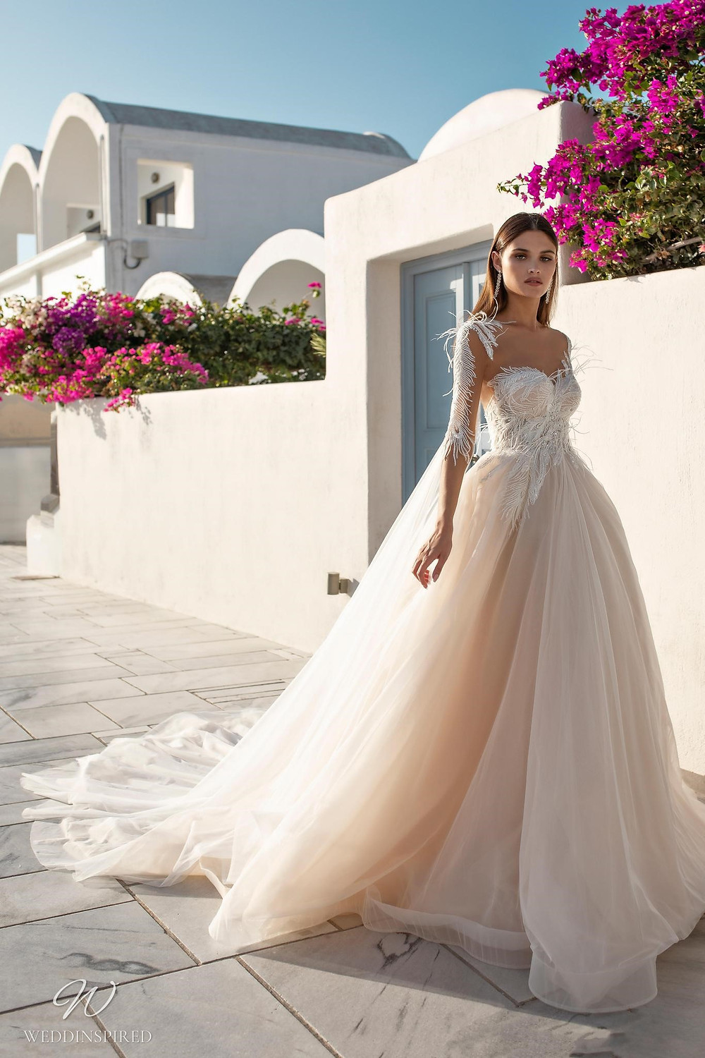 A Ricca Sposa romantic blush tulle ball gown wedding dress with a sweetheart neckline, long sleeves and feathers