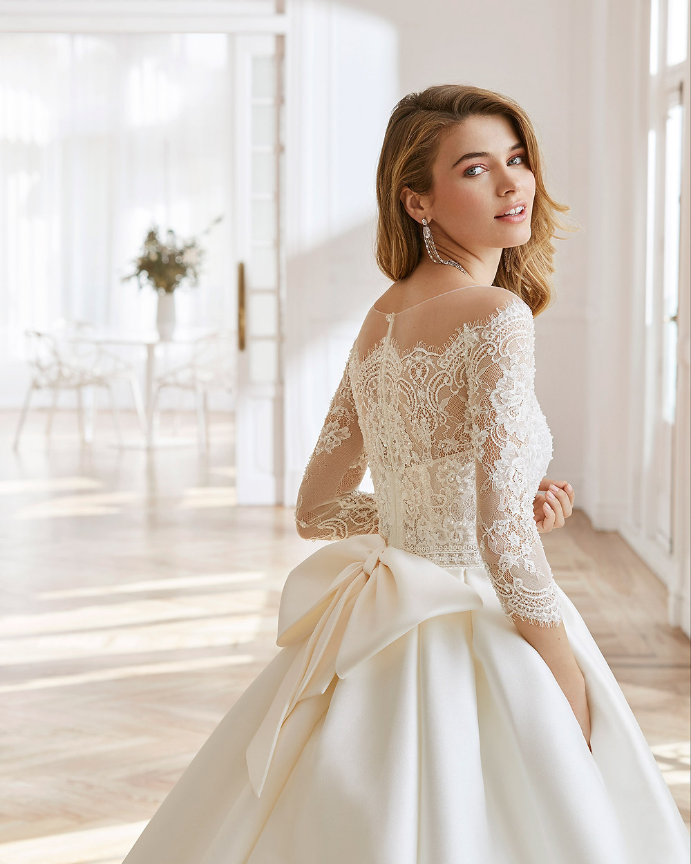 An Aire Barcelona 2020 ivory lace and silk off the shoulder ball gown wedding dress with long sleeves and a bow