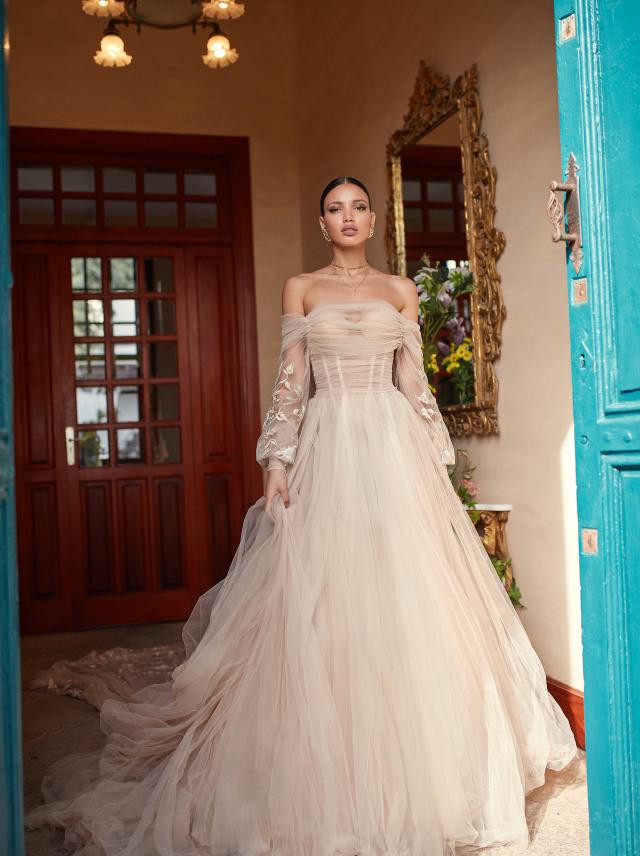 An off the shoulder, champagne, tulle, ball gown wedding dress with long sleeves