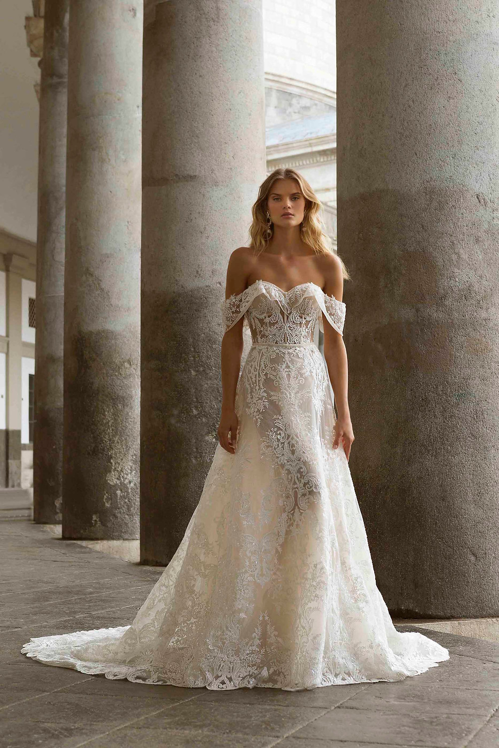 An ivory, off the shoulder, lace A-line wedding dress with corset top