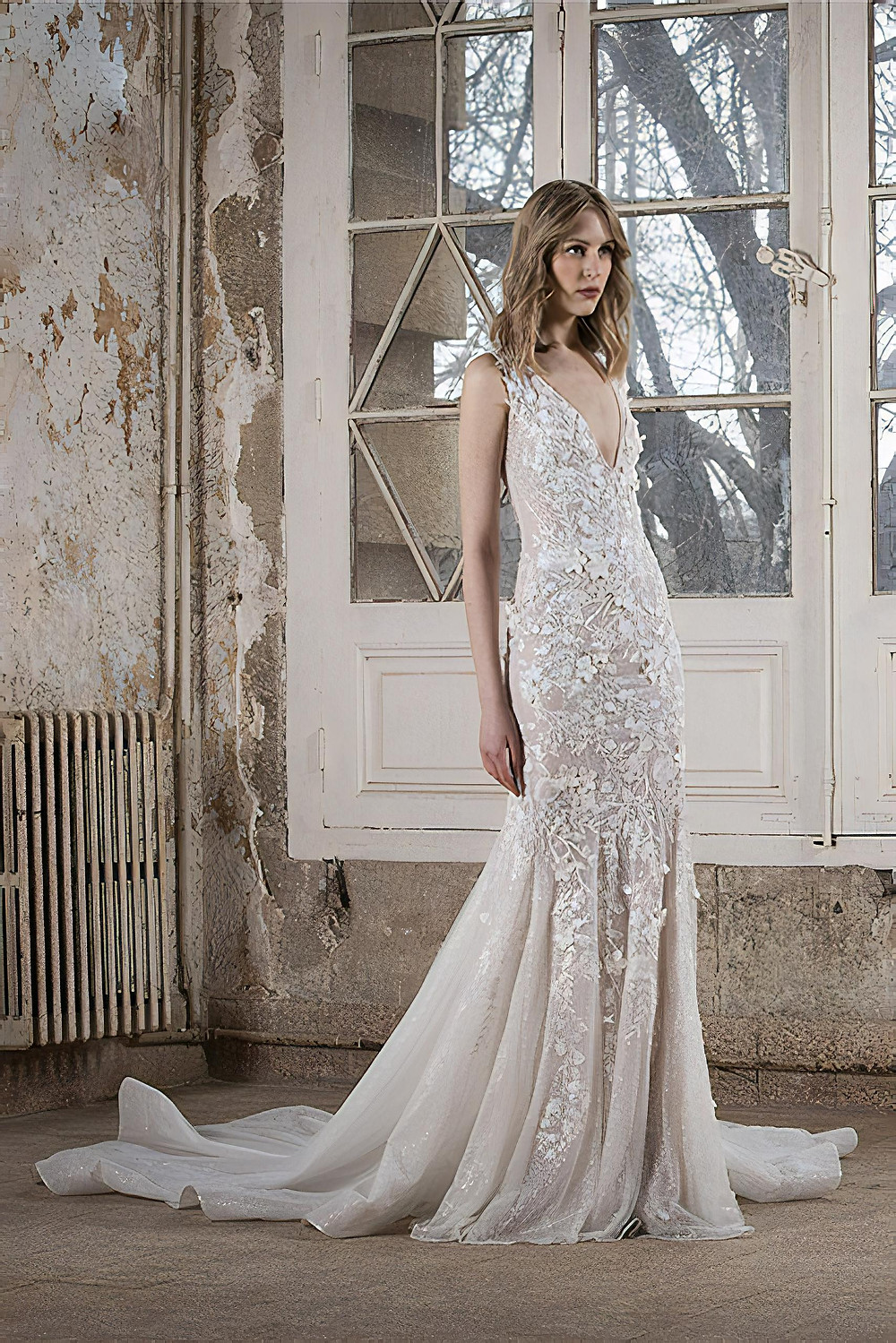 A fitted wedding gown with a deep-V, delicate floral embellishments and buttons detailing on the back