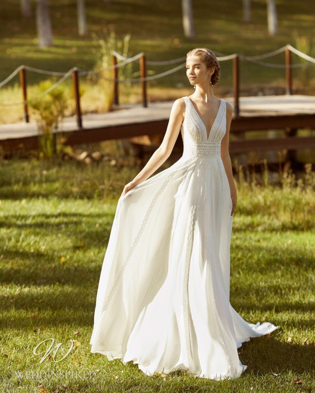 An Aire Barcelona 2021 flowy lace A-line wedding dress with a v neck