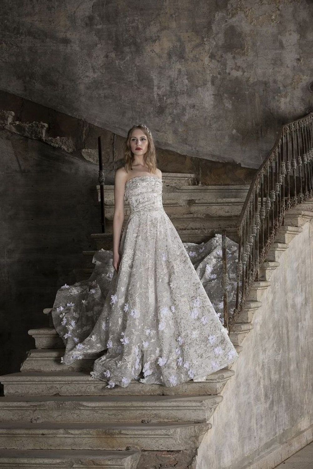 A strapless A-line wedding dress enriched with gold detailing and three-dimensional flower embellishments