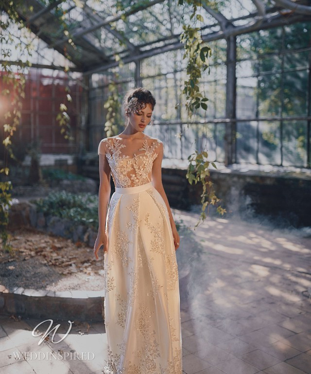 An Ange Etoiles 2021 ivory silk and lace A-line wedding dress with an illusion top