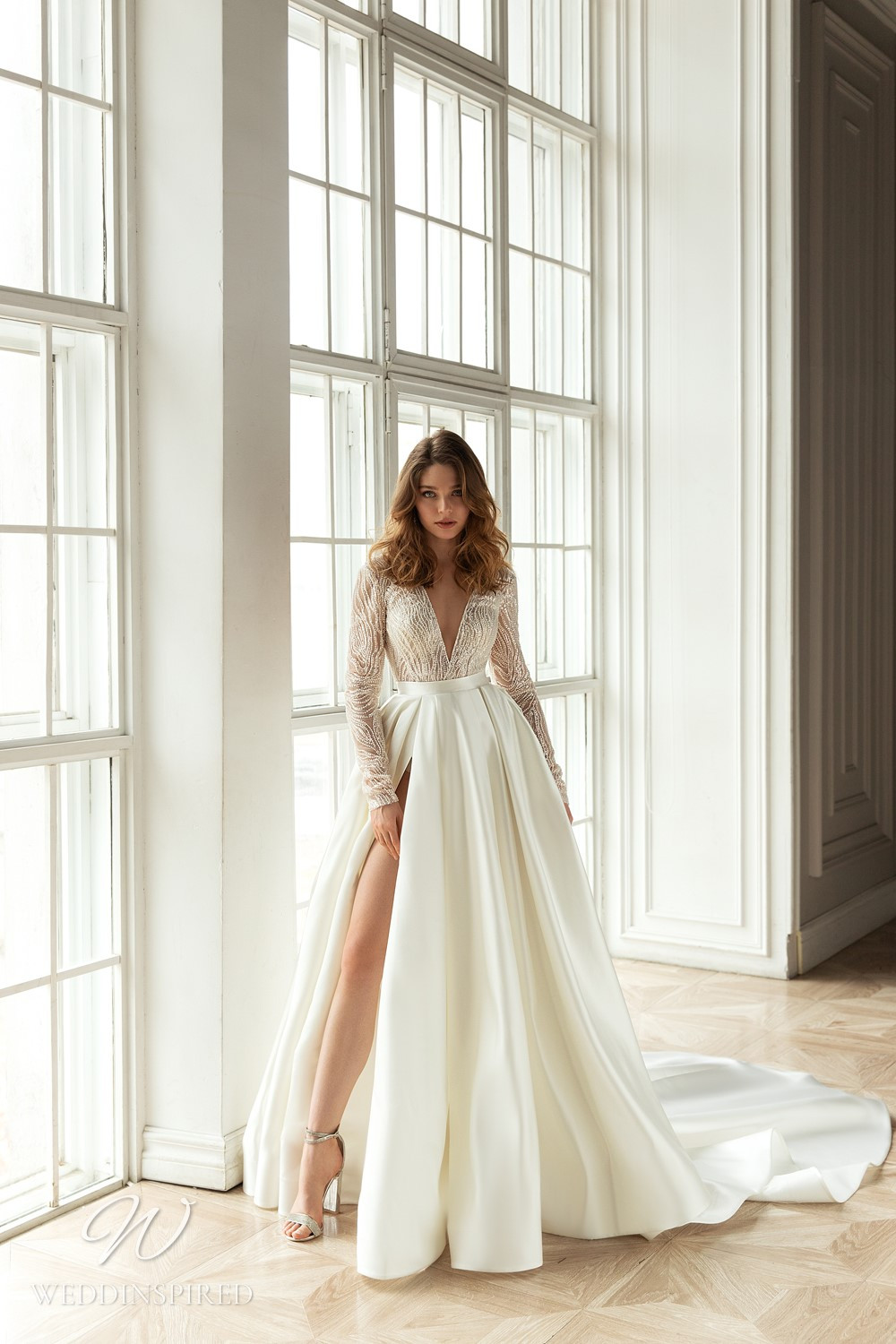 An Eva Lendel 2021 ivory silk ball gown wedding dress with long sleeves and a high slit