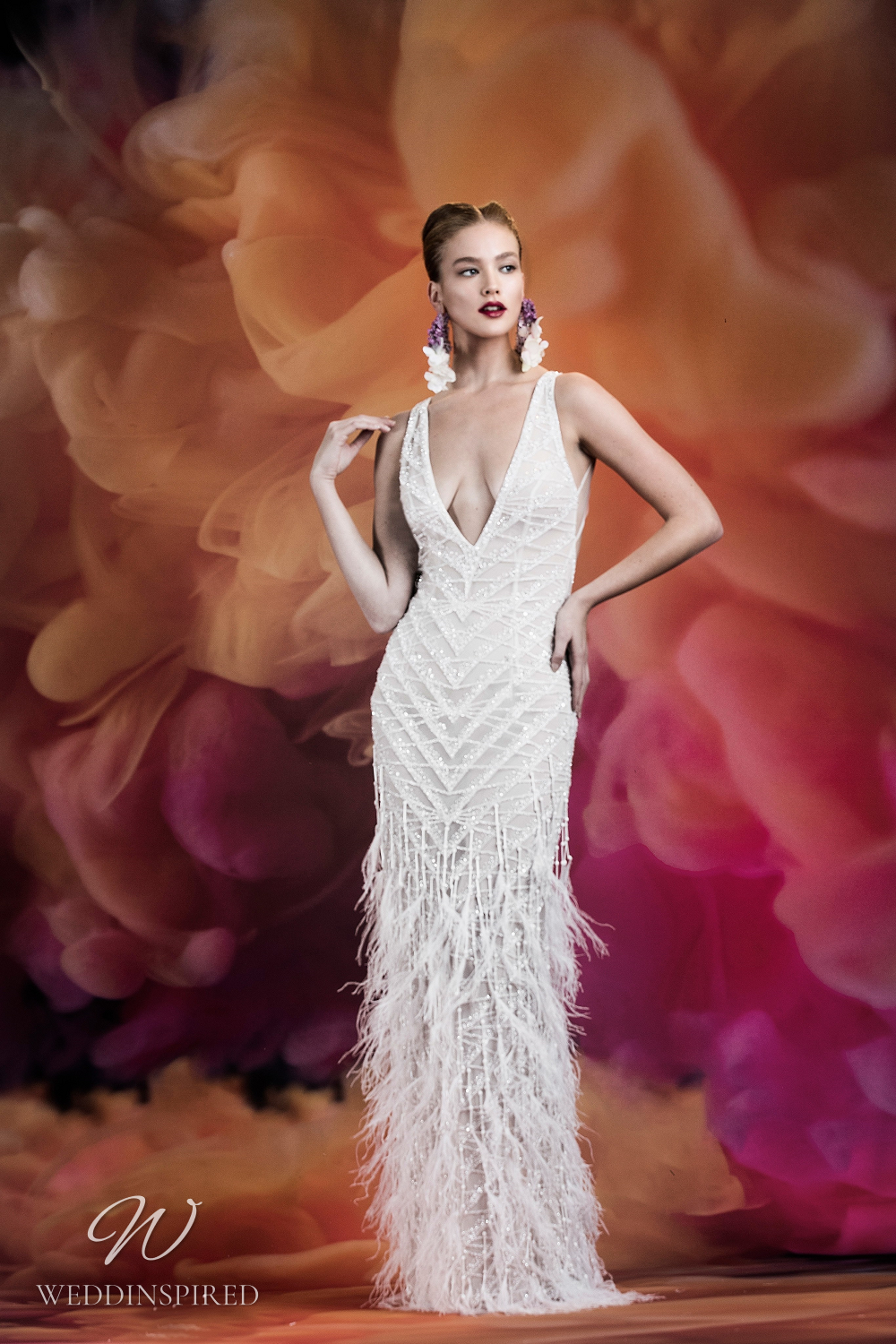 A Naeem Khan fitted vintage inspired wedding dress with feathers and a low v neckline