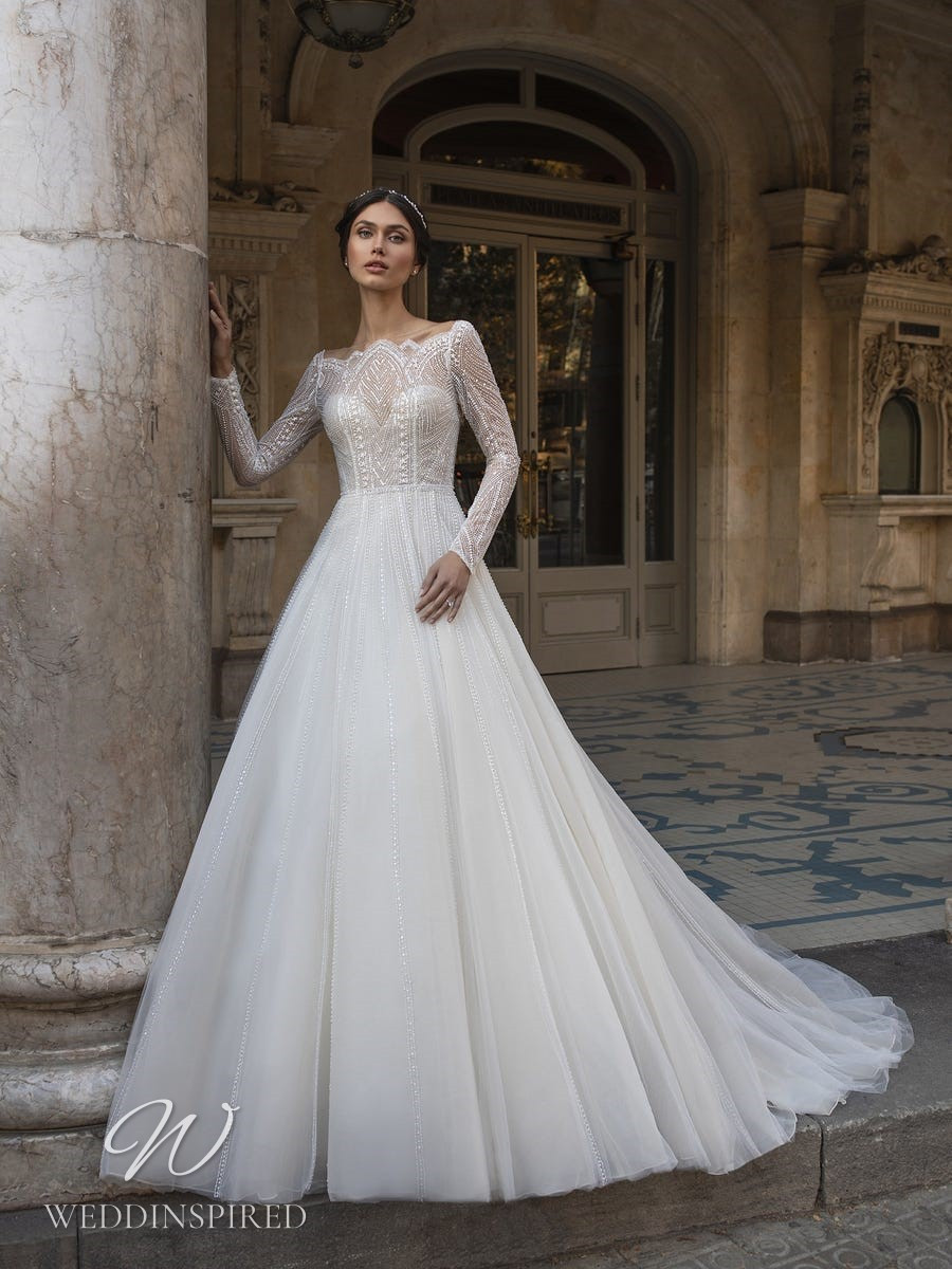 A Pronovias Privée 2021 sparkly tulle ball gown wedding dress with long sleeves and a scallop neckline