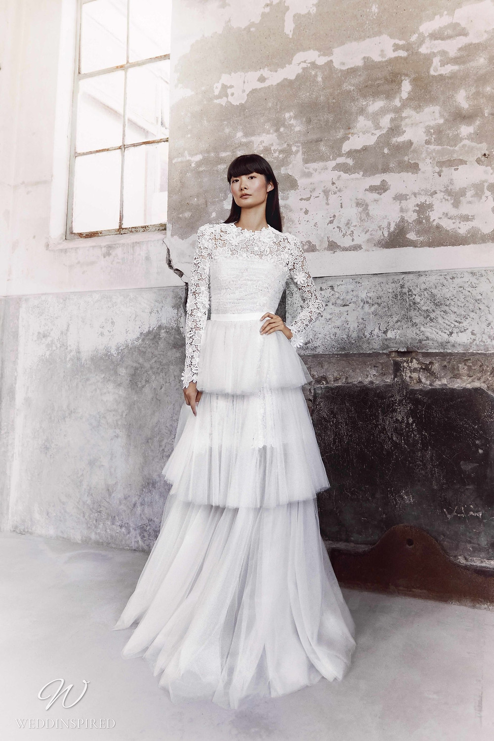 A Viktor & Rolf Fall/Winter 2021 modest lace and tulle A-line wedding dress with long sleeves, a high neckline and a layered ruffle skirt