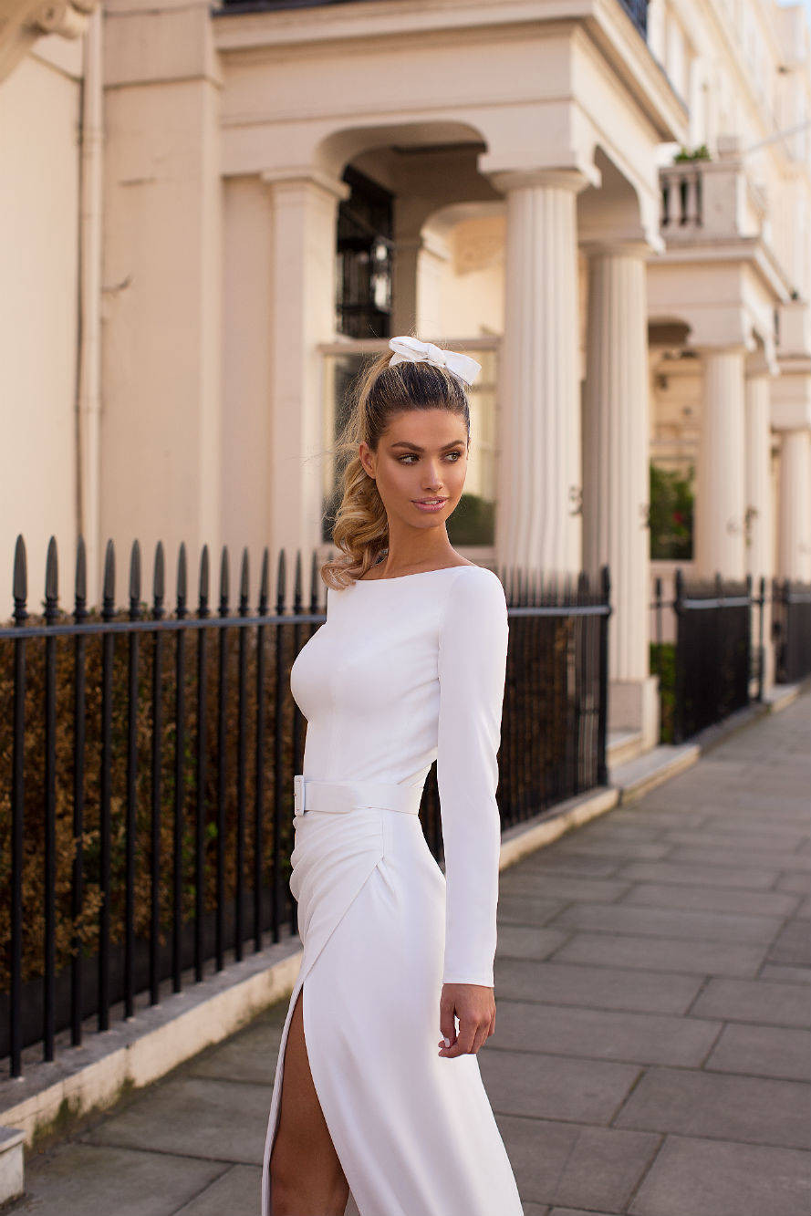 A Milla Nova simple fitted wedding dress with long sleeves and a high slit