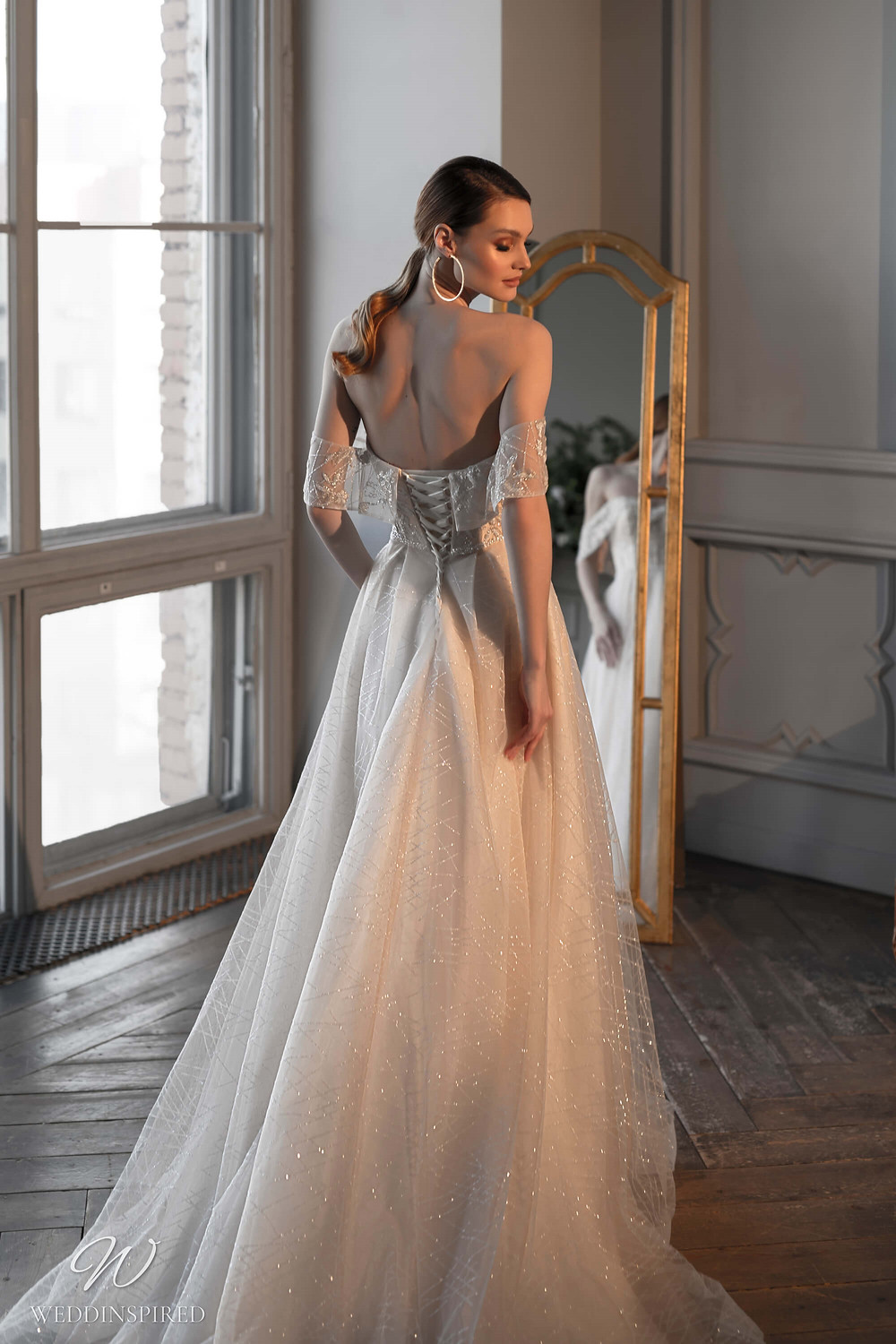 A Naviblue Bridal 2021 sparkly blush mesh off the shoulder A-line wedding dress with a corset top
