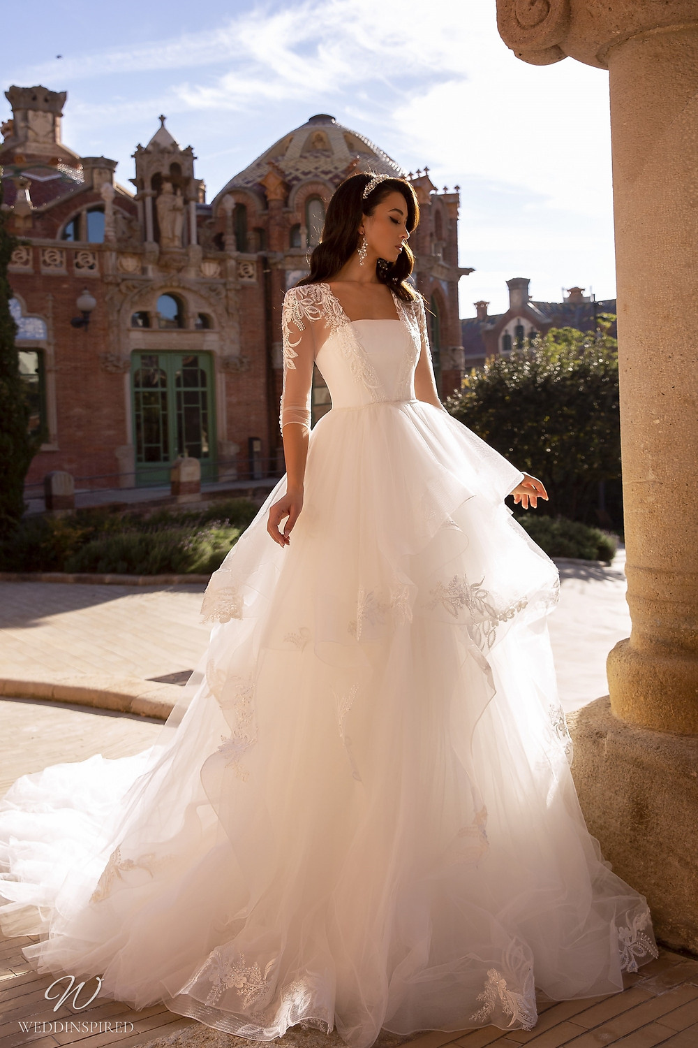 A Maks Mariano tulle ball gown wedding dress with ruffle skirt and long sleeves