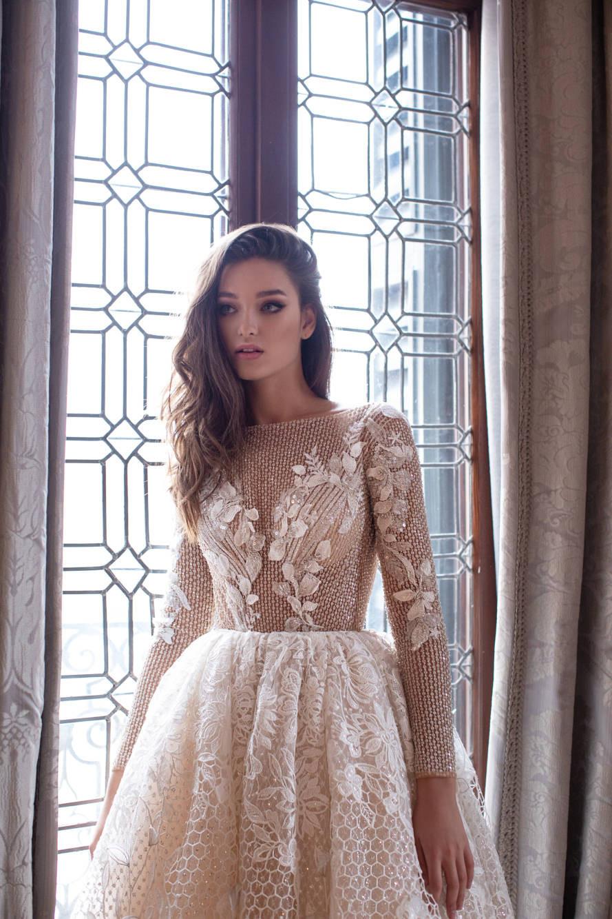 A Milla Nova blush gold princess ball gown wedding dress with long sleeves