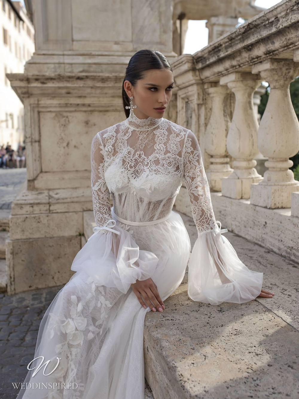 A Pinella Passaro lace and tulle ball gown wedding dress with long sleeves and a high neck