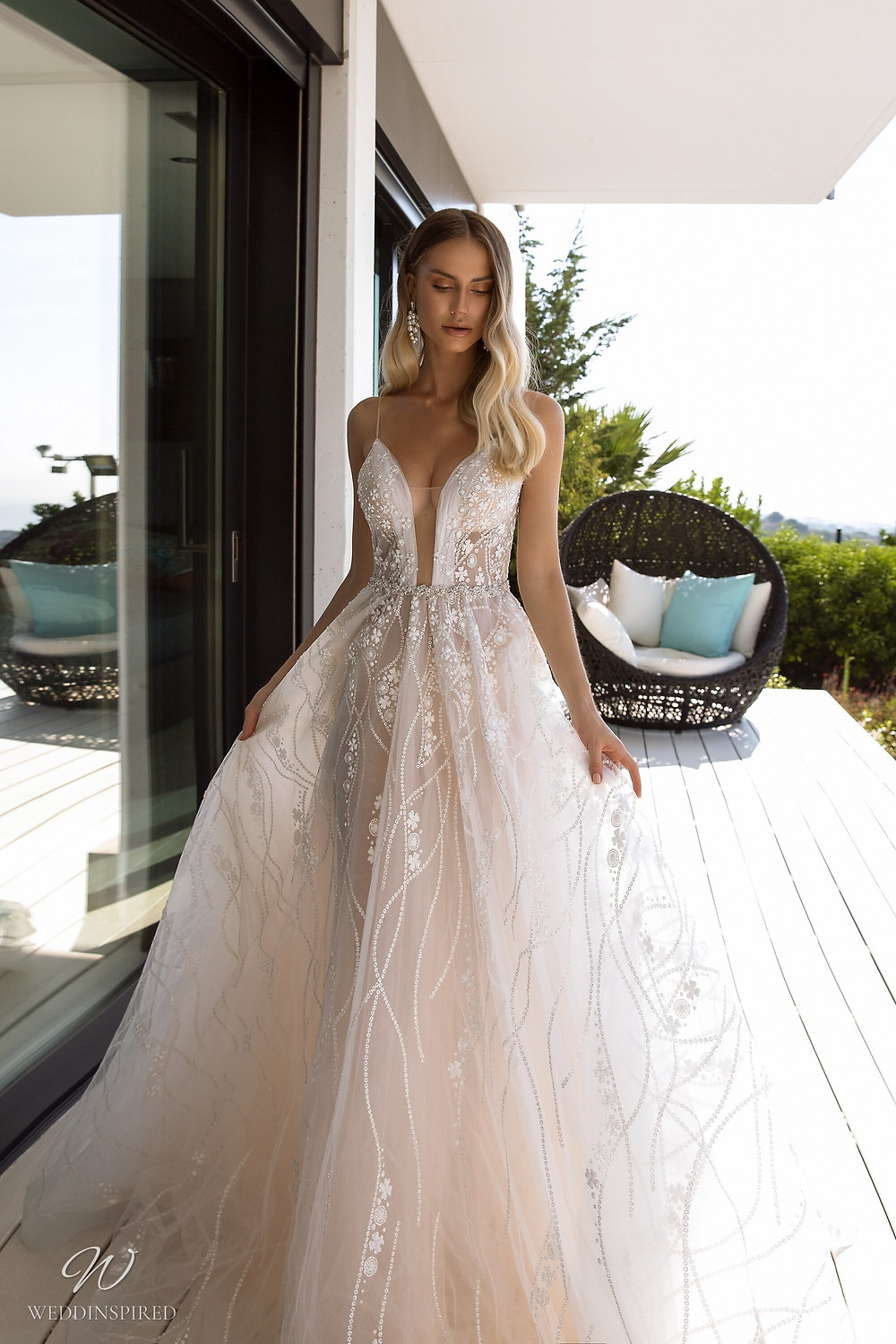 A Tina Valerdi blush tulle A-line wedding dress with a low neckline and thin straps