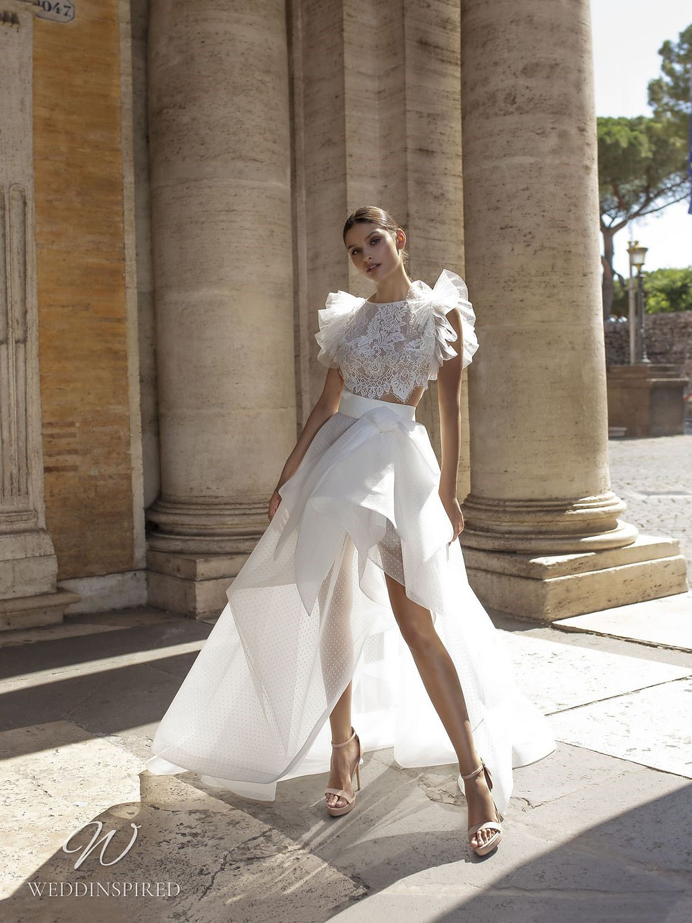 A Pinella Passaro lace and tulle A-line wedding dress with a bow and a high slit