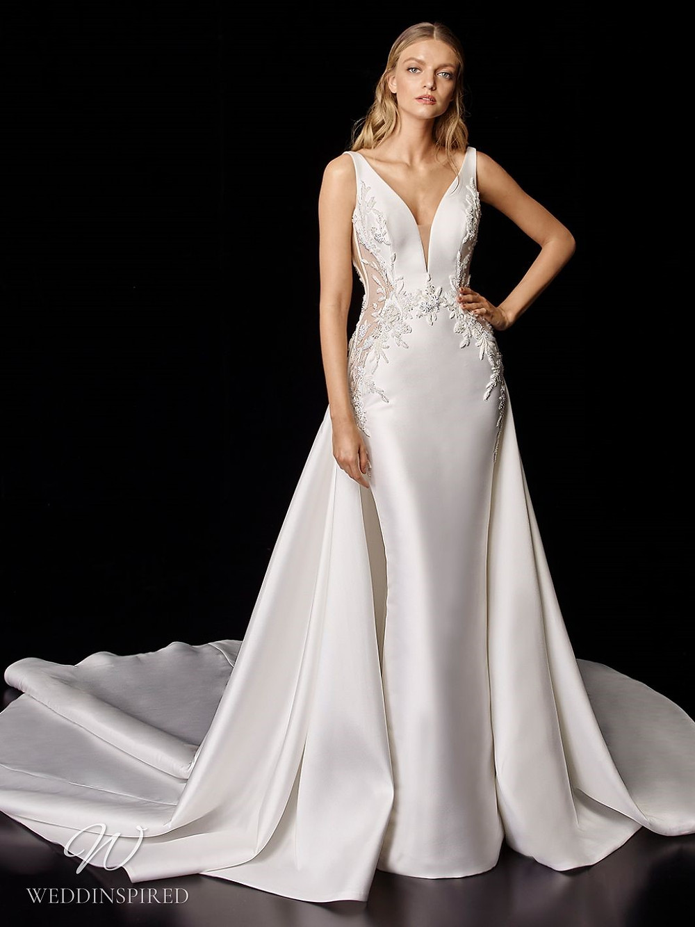 An Enzoani silk column wedding dress with lace illusion inserts, a v neckline and a cape with a train