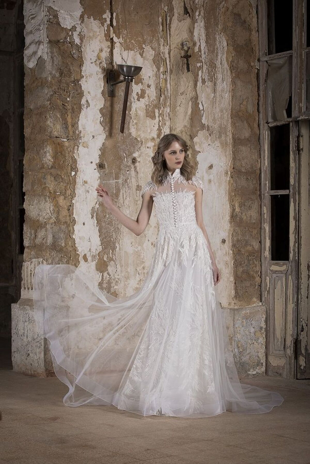 A collared A-line wedding gown, enriched with button detailing and delicate beaded embroidery