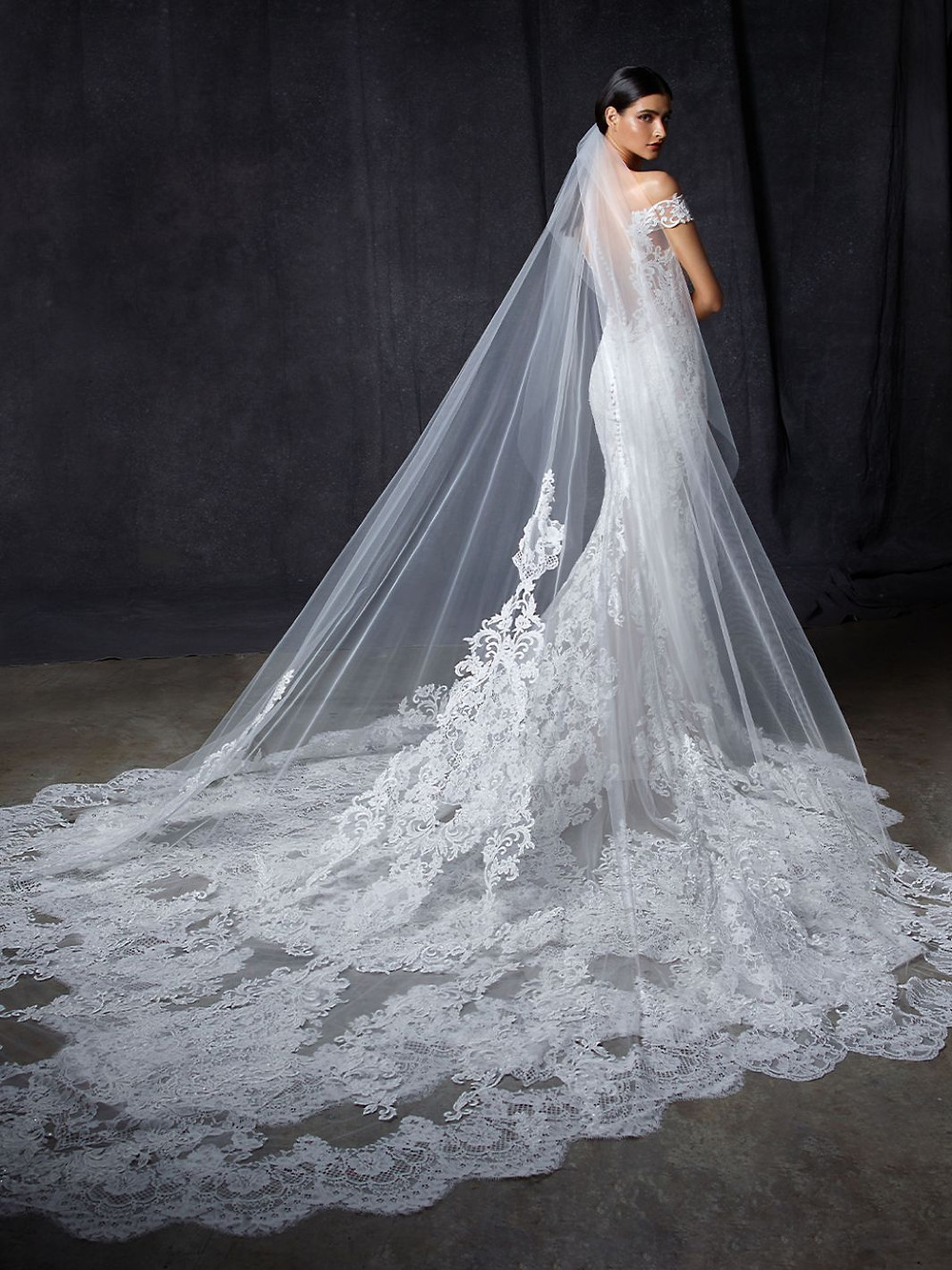 An Enzoani off the shoulder lace mermaid wedding dress with a long train and veil