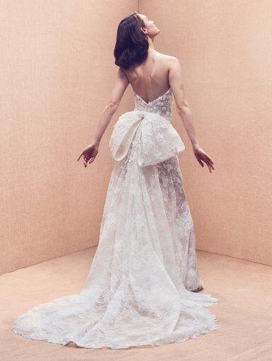 An Oscar de la Renta strapless lace A-line wedding dress with a bow and a train