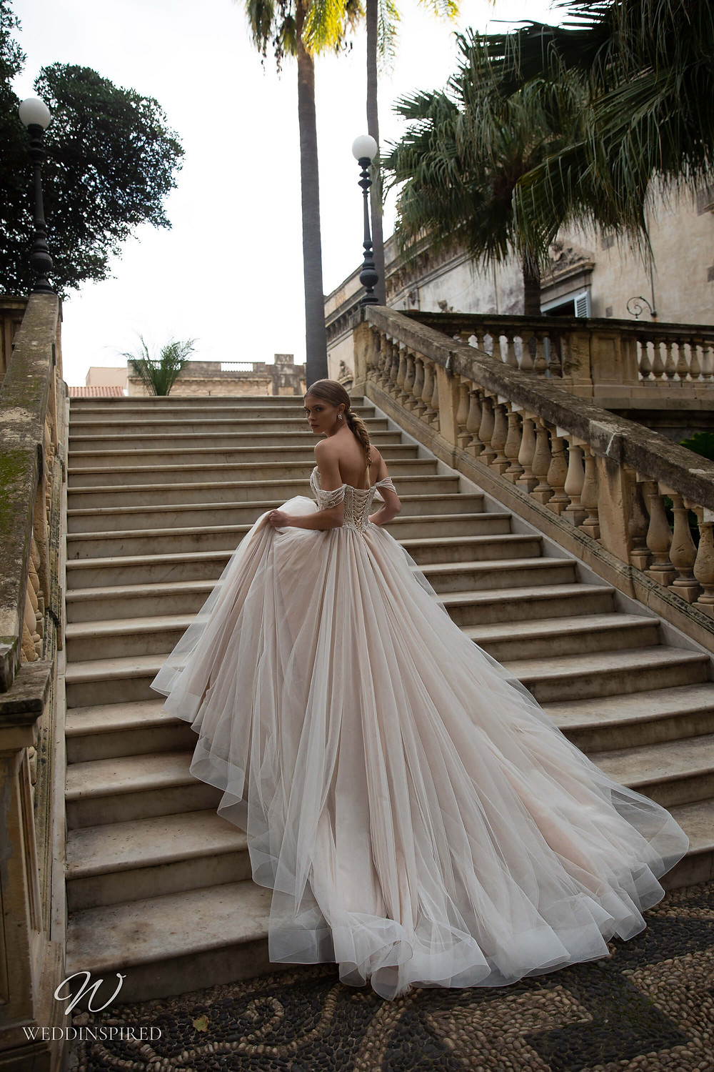A Naviblue blush off the shoulder tulle ball gown wedding dress with a corset