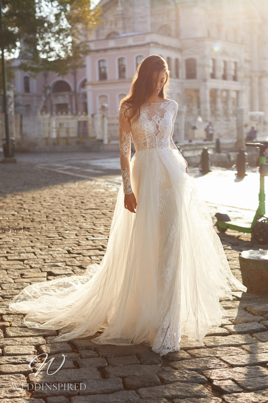 A Milla Nova 2021 ivory lace and tulle A-line wedding dress with long sleeves and a high neckline