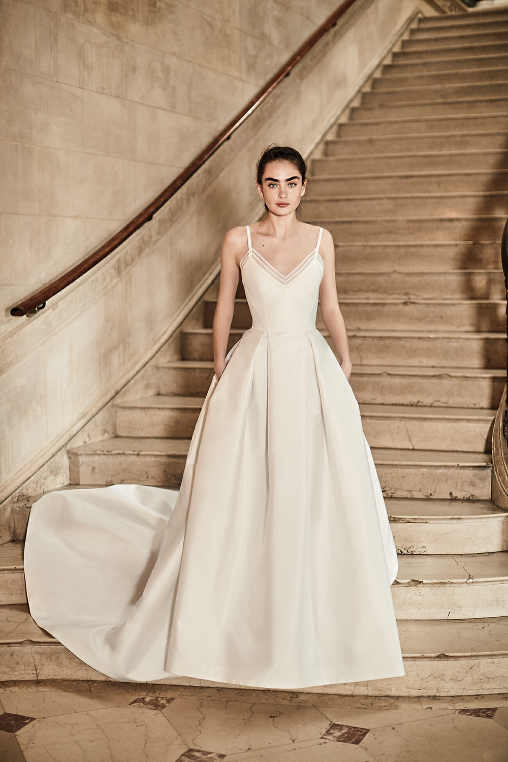 A Carolina Herrera simple ivory ball gown wedding dress with pockets and straps